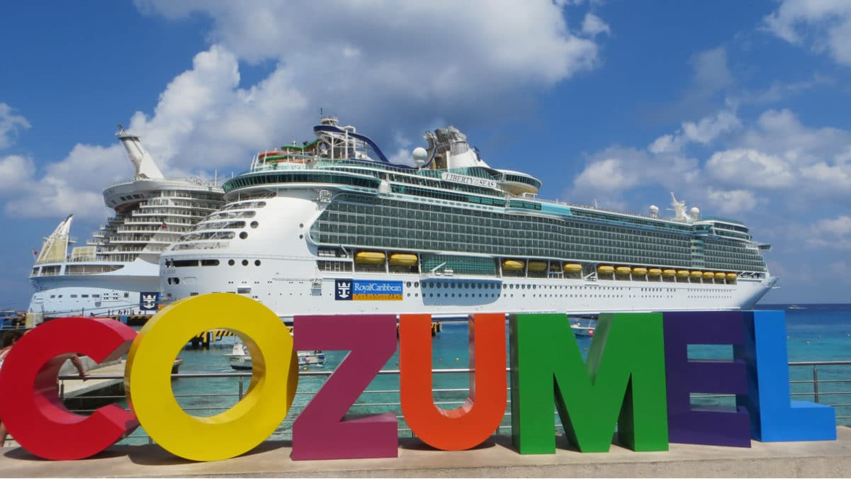 Cruise ship docked in front of sign in Cozumel